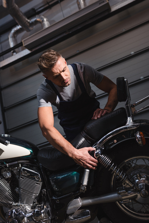 serious mechanic checking back wheel in garage Banque d'images - 112991793