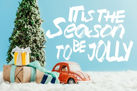 close-up shot of toy red car with presents and christmas tree standing on snow made of cotton on blue background with it is the season to be jolly inspiration