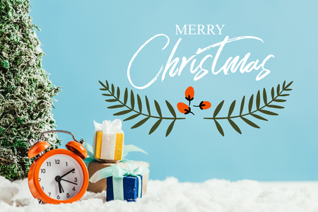 close-up shot of christmas gifts with alarm clock and miniature christmas tree standing on snow on blue background with merry christmas lettering with leaves illustration Reklamní fotografie
