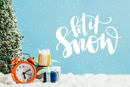 close-up shot of christmas gifts with alarm clock and miniature christmas tree standing on snow on blue background with let it snow lettering