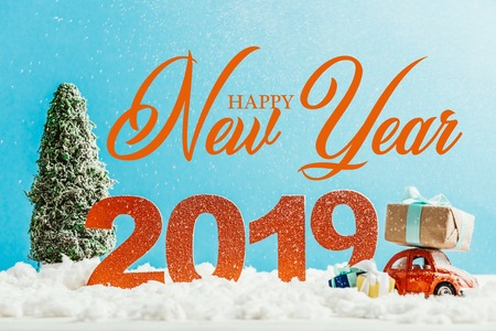 big red 2019 numbers with toy car, gifts and christmas tree on snow with happy new year lettering Stock Photo