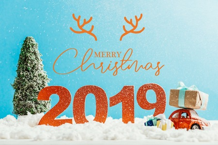 big red 2019 numbers with toy car, gifts and christmas tree on snow with merry christmas lettering