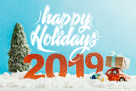 big red 2019 numbers with toy car, gifts and christmas tree on snow with happy holidays lettering Stock Photo