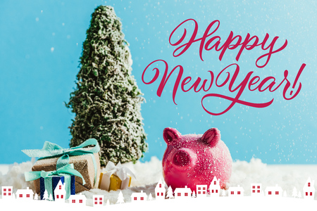 miniature christmas tree with gifts and piggy bank standing on snow on blue background with happy new year lettering with houses illustration