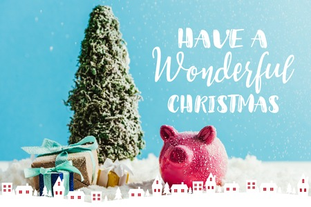 miniature christmas tree with gifts and piggy bank standing on snow on blue background with have a wonderful christmas inspiration with houses illustration 版權商用圖片