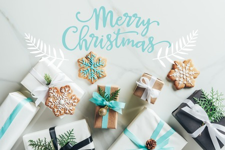 "flat lay with christmas gift boxes and snowflake cookies on marble background with ""merry christmas"" lettering"