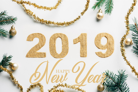 top view of 2019 year sign, pine branches, golden garlands and christmas balls on white background with