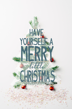 top view of green pine branch decorated as festive christmas tree with glitters on white background with have yourself a merry little christmas inspiration