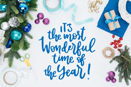 top view of handmade christmas wreath decorations and scissors isolated on white with its the most wonderful time of the year inspiration Stock fotó