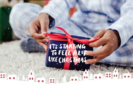 cropped image of african american child in pajamas opening christmas gift on floor with it is starting to feel a lot like christmas lettering, snow and houses illustration