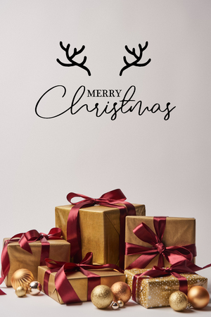 gift boxes with burgundy ribbons and golden christmas balls isolated on white with merry christmas lettering with deer horns
