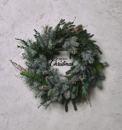 fir wreath for Christmas decoration hanging on grey wall with