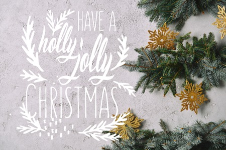 cropped image of handmade Christmas tree with snowflakes hanging on grey wall with have a holly jolly christmas inspiration Imagens