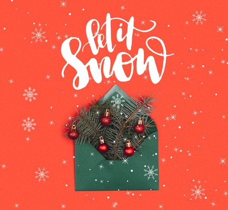 close-up view of green envelope with fir twigs and shiny christmas baubles isolated on red with let it snow lettering and snowflakes