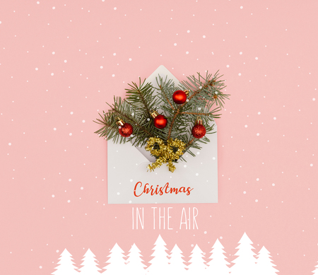 top view of white envelope with fir twigs and shiny christmas baubles isolated on pink with christmas in the air inspiration, snow and christmas trees illustration