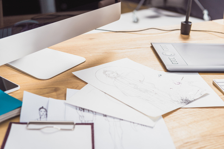Work table of designer with sketches and computer
