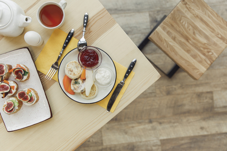 top view of healthy delicious breakfast with tea set on wooden table