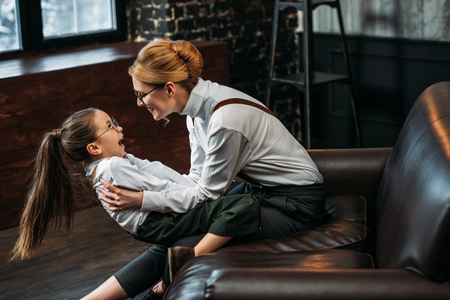 happy mother and daughter playing on couch at home 스톡 콘텐츠 - 113354639