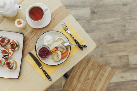 top view of tasty healthy breakfast with tea set on wooden table Stock Photo