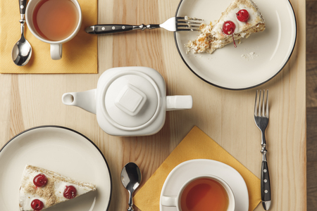 top view of teapot, two cups with hot tea and delicious cakes on plates Stock Photo