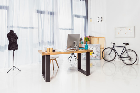 Spacious home office with working table and bicycle 스톡 콘텐츠