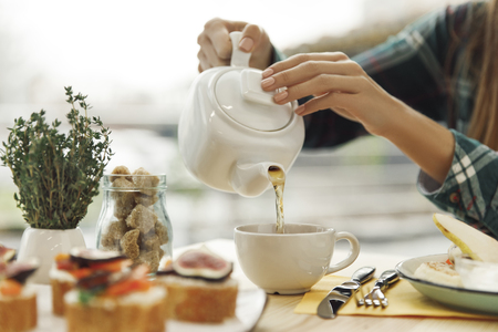 close-up partial view of woman pouring tea from teapot during breakfast