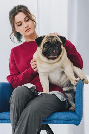 Pretty lady cuddling pug in chair