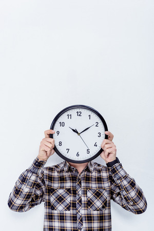 Clock in male hands over his face  isolated on white Stock Photo