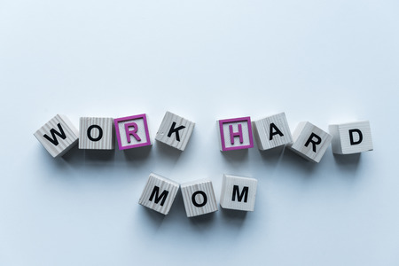 top view of wooden cubes with words Work Hard Mom on blue table Reklamní fotografie - 113354844