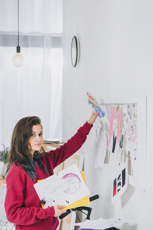 Young woman pinning sketches on mood board