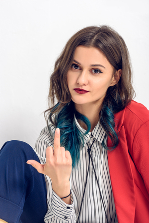 Pretty lady showing middle finger on white background