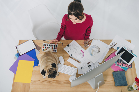 Young woman working with sketches with cute pug on working table with computer Banco de Imagens