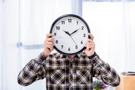 Man holding clock over face in front of window