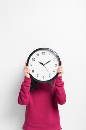Girl holding clock over her face isolated on white Stock fotó