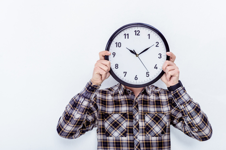 Man holding clock over face isolated on white