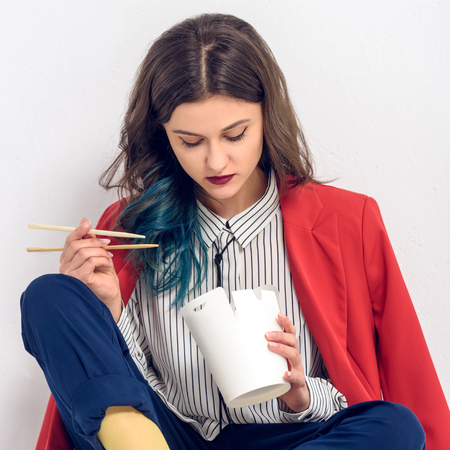 Young stylish woman looking at carton with Chinese food