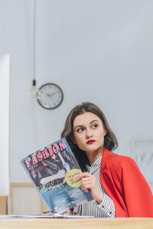 Pretty lady reading fashion magazine Stock Photo