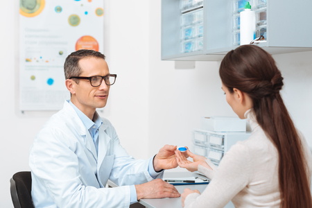 side view of ophthalmologist in eyeglasses giving contact lens to patient in clinic Standard-Bild