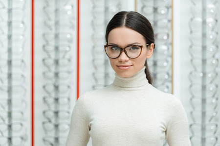 portrait of beautiful young woman in eyeglasses looking at camera in optics Stock Photo