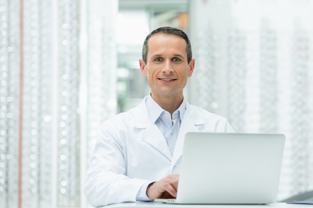selective focus of smiling oculist in white coat sitting at table with laptop in optics