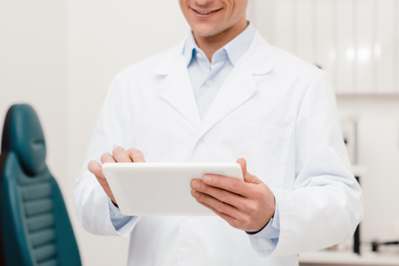 partial view of smiling doctor in white coat using digital tablet in clinic Foto de archivo - 113355177