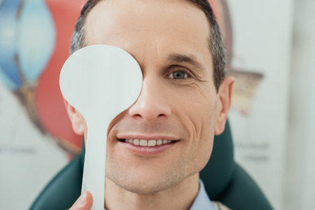 obscured view of smiling man getting eye test in clinic Stock Photo