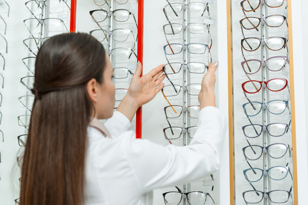 selective focus of optometrist taking eyeglasses from shelf in optics Archivio Fotografico