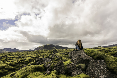 young woman sitting on rock and looking at majestic icelandic landscape