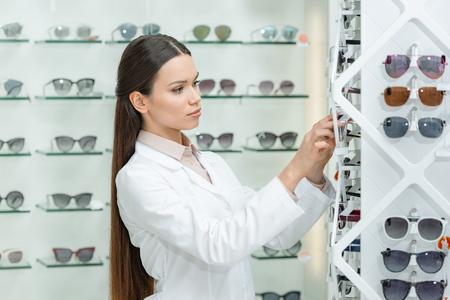 side view of optometrist taking eyeglasses from shelf in optics Stock Photo