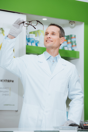 portrait of smiling optometrist in white coat looking at eyeglasses in hands in optics Foto de archivo