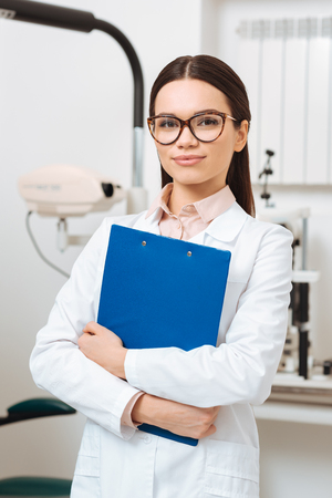 portrait of smiling optometrist in white coat with notepad in hands looking at camera in clinic