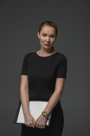 beautiful kazakh businesswoman holding clipboard and looking at camera isolated on grey
