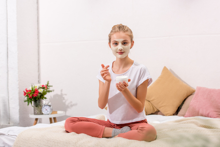 young woman applying clay mask on face while sitting on bed at home Foto de archivo - 114245937