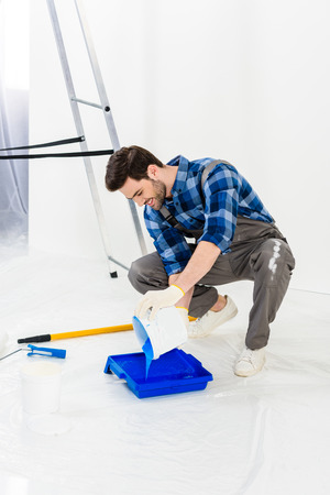 smiling man pouring paint from bucket into plastic paint tray